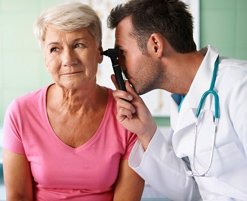 ENT looking in senior woman's ear