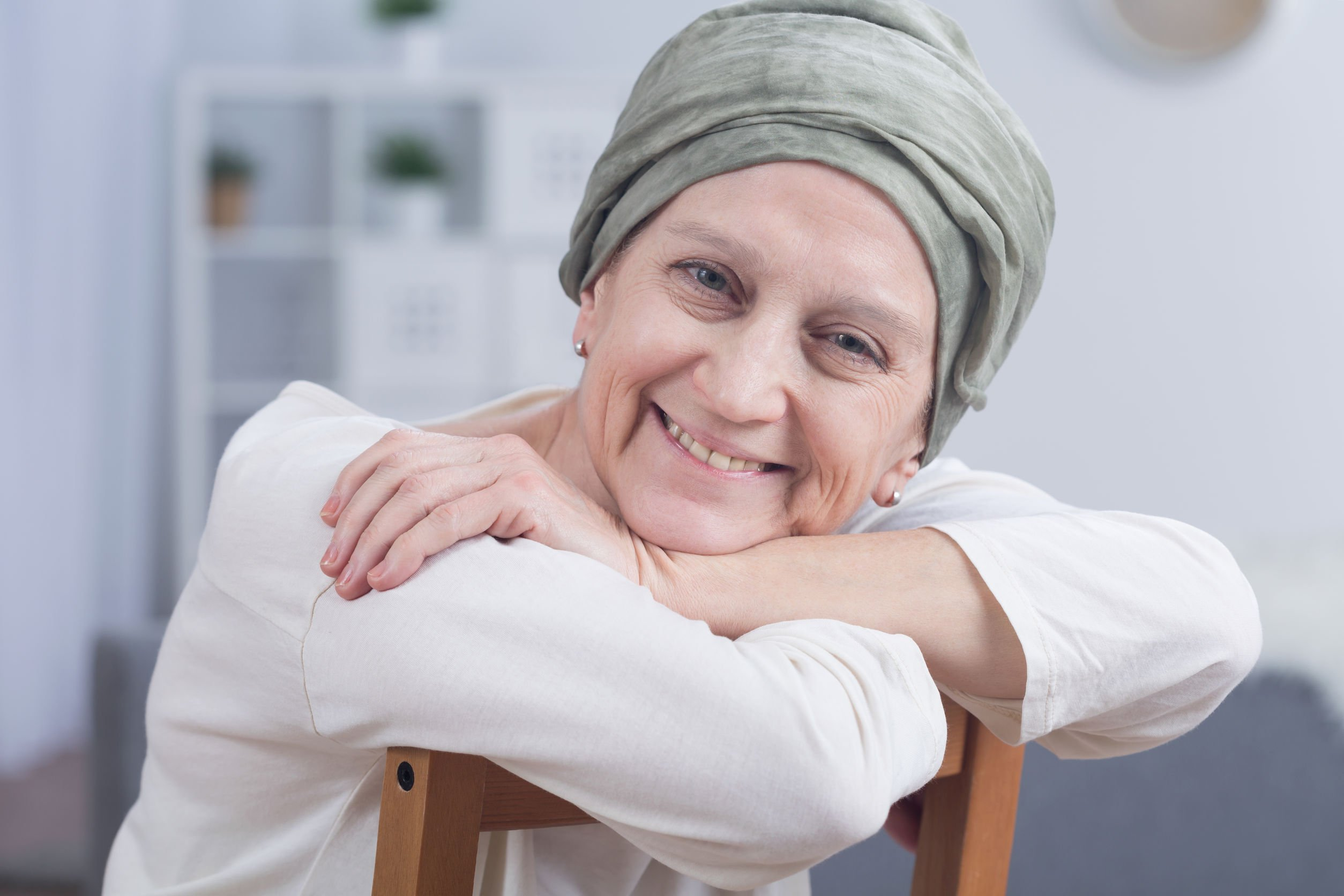 cancer survivor sitting in a chair smiling with a head scarf