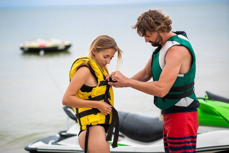 man putting life jacket on woman for water safety