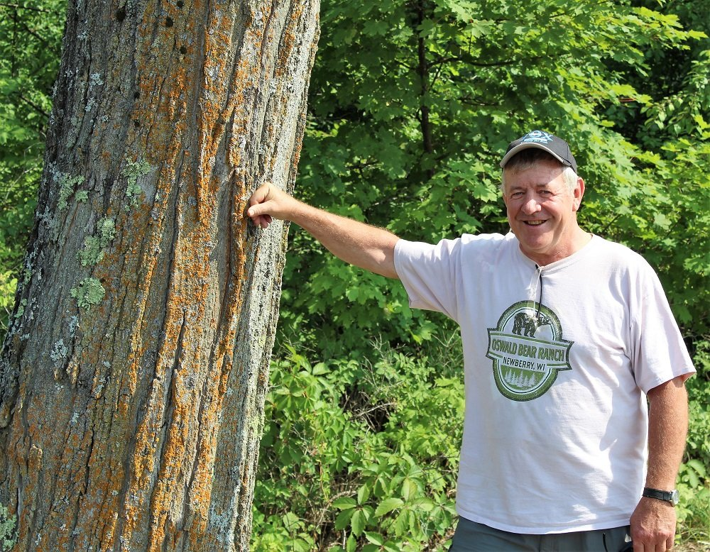 Jack Hubbard standing next to a tree