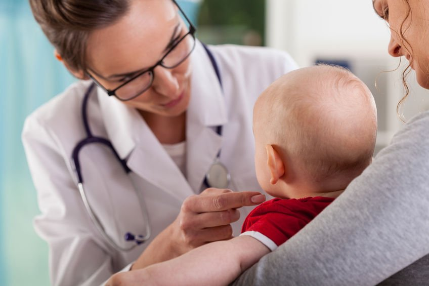 mother holding baby sick with rsv at doctor's office