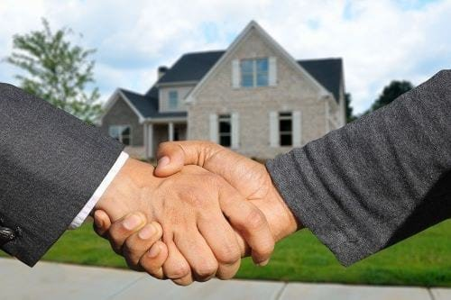 Shaking hands in front of a house
