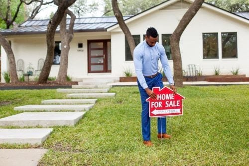 Man putting a home for sale sign in yard