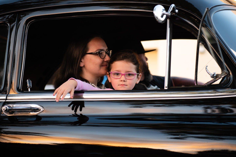 child sitting in parents lap in car
