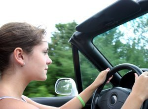 A young woman practicing mindful driving behind the wheel.