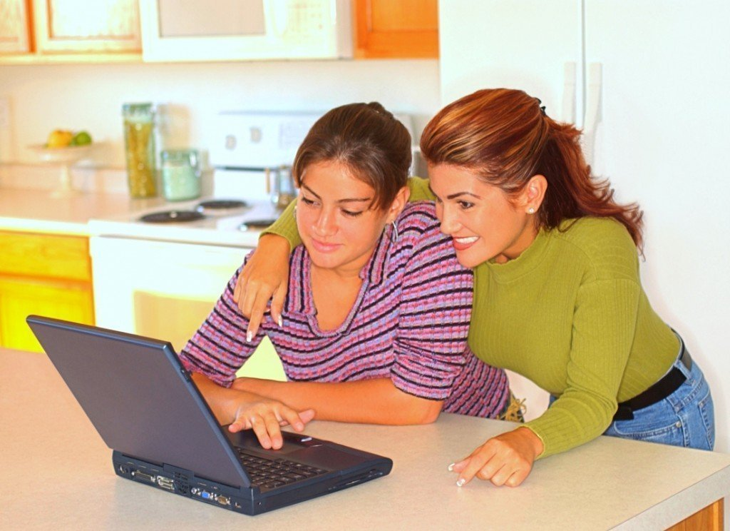 Teen girl and mom using a computer to learn about defensive driving.