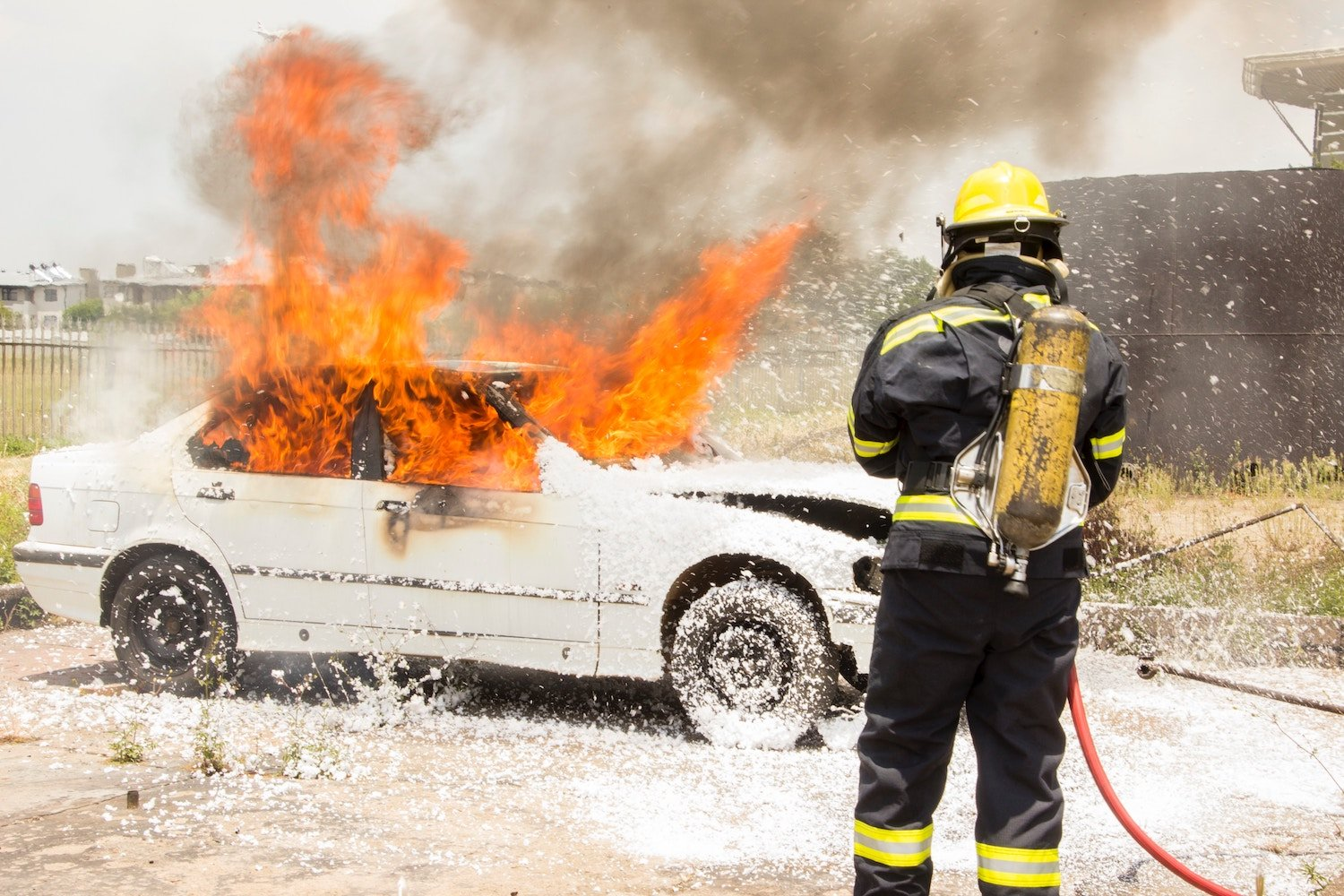 firefighter putting out burning car