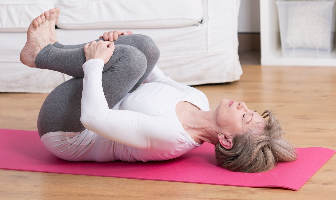 Woman on a on her back on yoga mat on floor pulling her knees to her chest to stretch