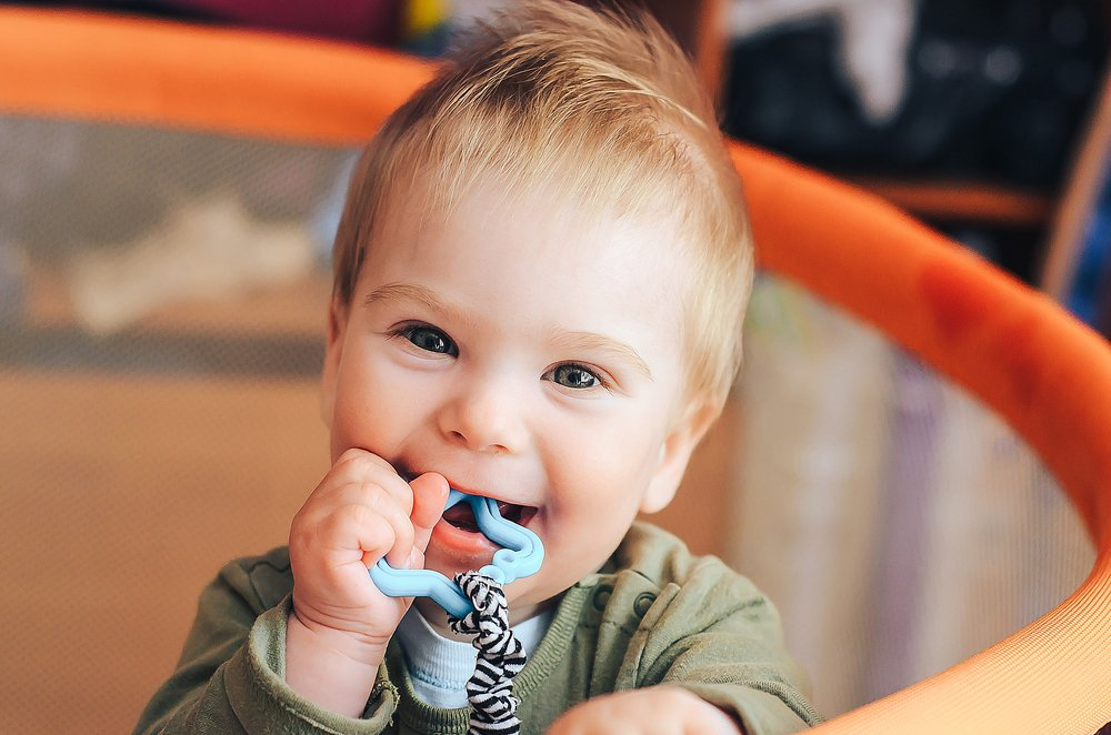 Teething Baby Chewing on Toy