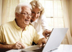 A smiling senior couple on their laptop with her pointing out something to him.