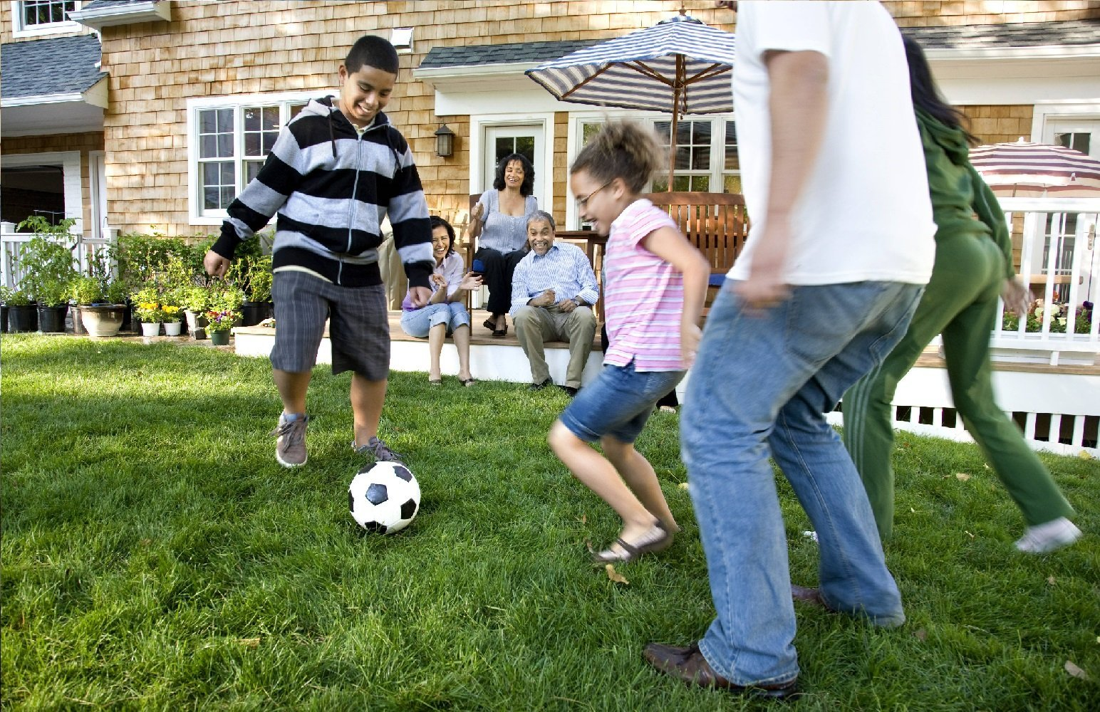 Family with secondary health insurance playing soccer