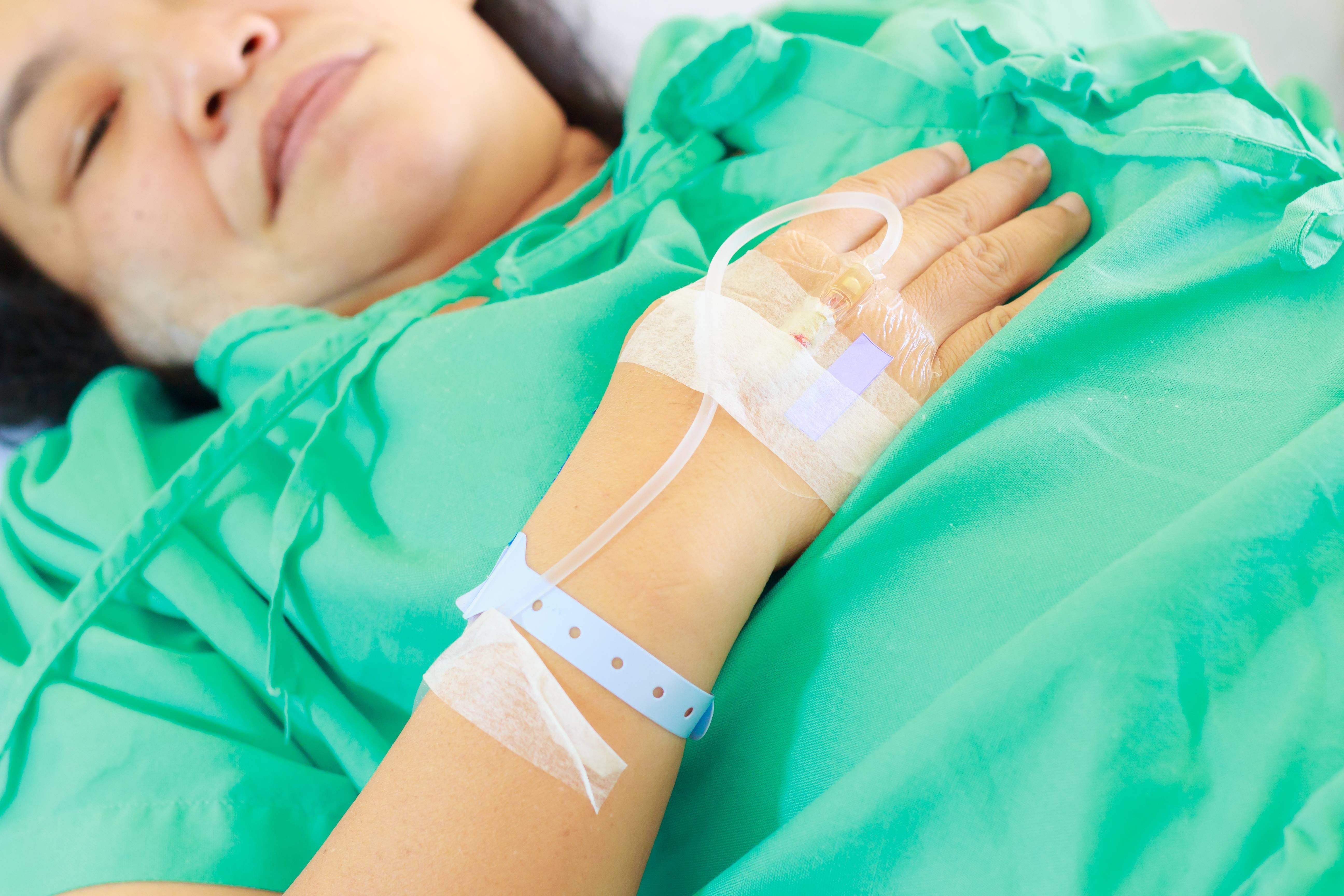 Sick woman with secondary health insurance in hospital gown with I.V.