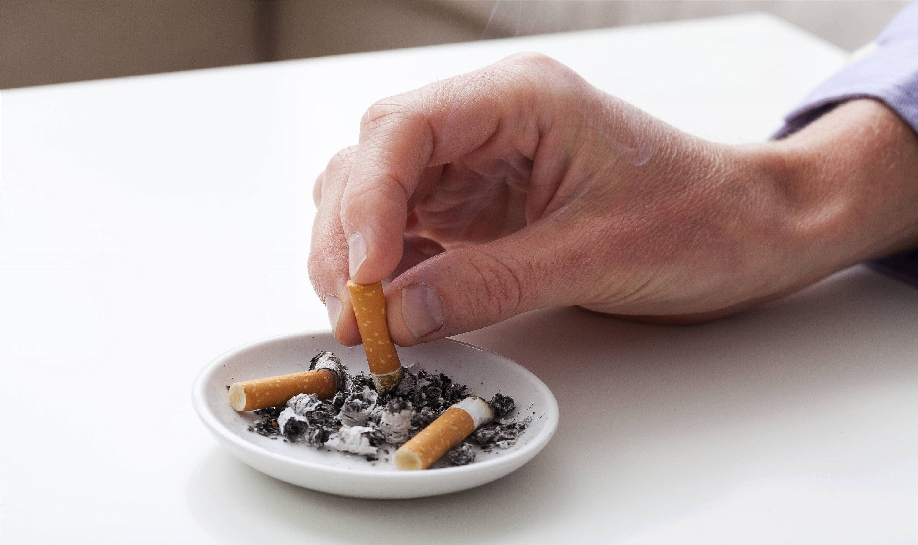 Hand blotting out cigarette in ashtray after learning about smoking and health insurance