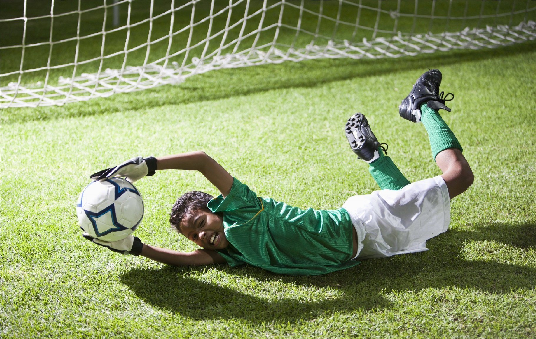 Young boy with supplemental accident insurance in green shirt wearing white gloves diving in front of soccer cage