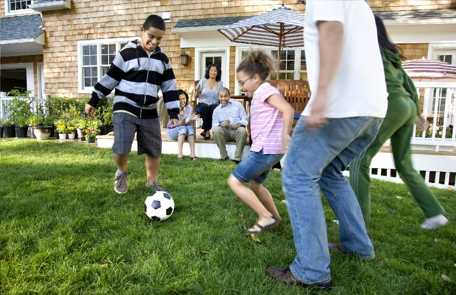 happy family with health insurance playing soccer