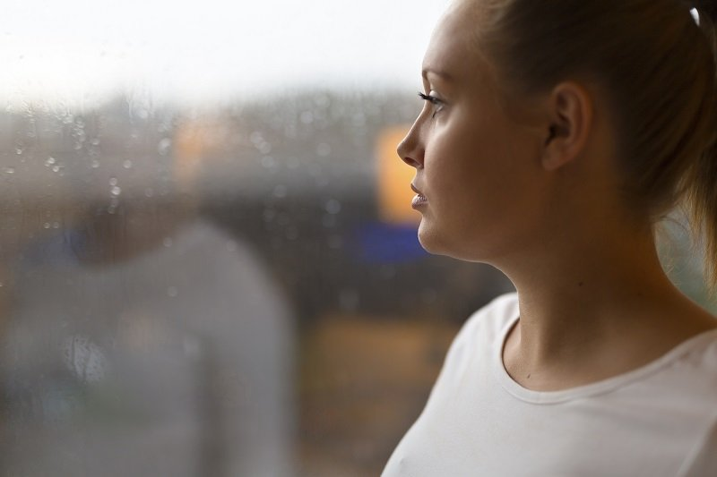 Young woman with thoughtful expression looking out the window.
