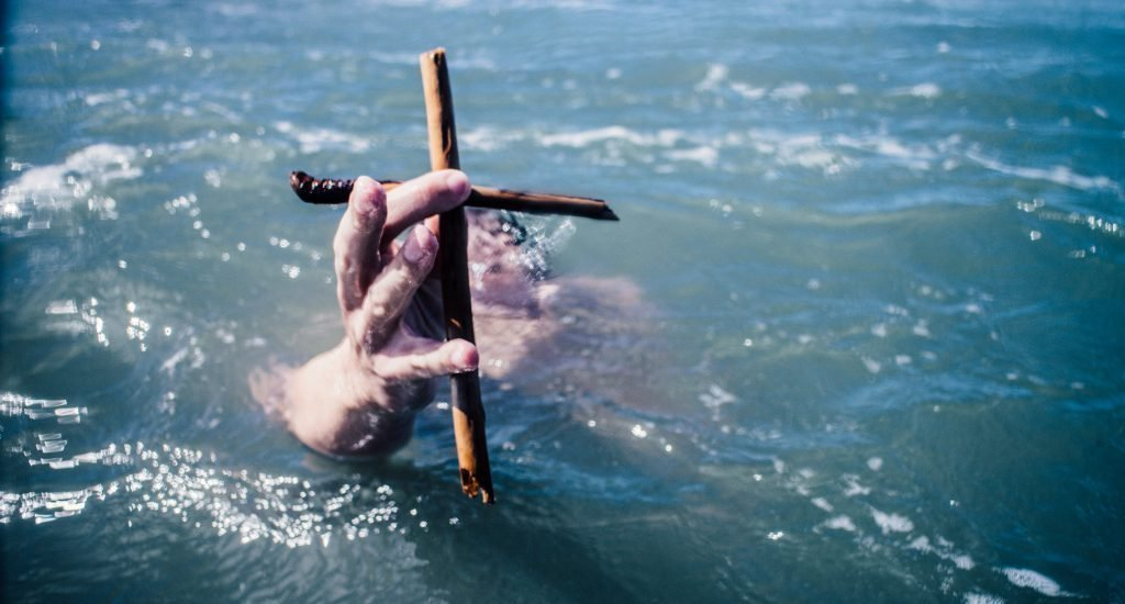 Drowning man with cross