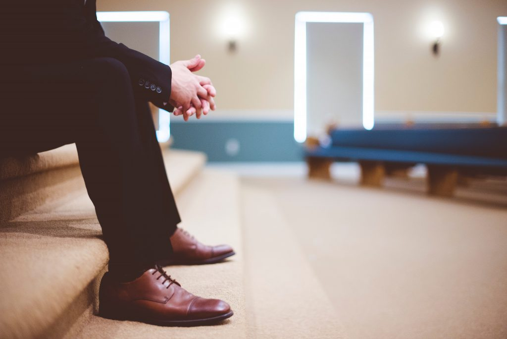 Closeup of man sitting on steps in church wearing black dress slacks and brown leather shoes with hands folded in prayer