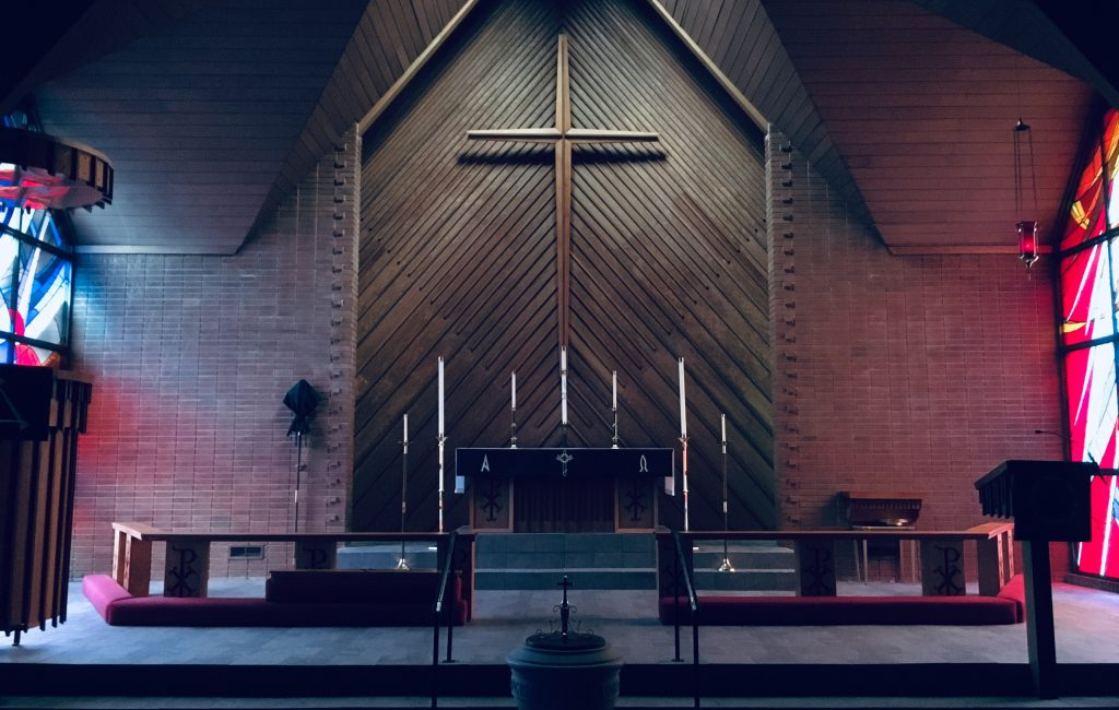 dimly lit interior of a brown brick church with wooden cross at front
