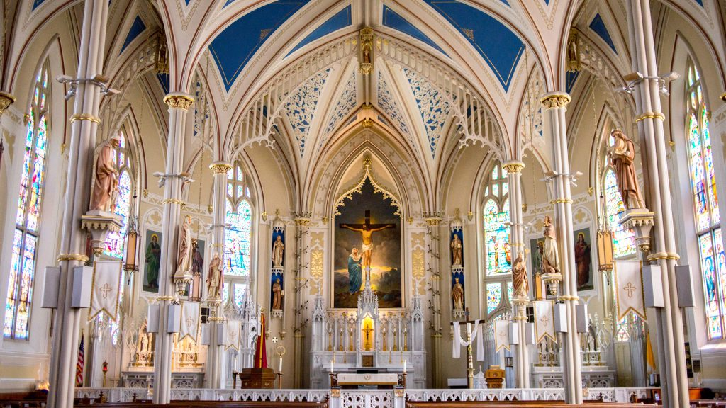interior of beautiful, brightly-lit white cathedral with colorful icons and statues of saints, stained glass windows, and painting of a crucifix at the front